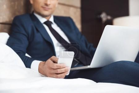 Businessman on bed with phone and laptop