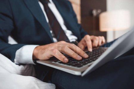 Photo pour Recadrée tir d'homme d'affaires en costume formel assis sur le lit et à l'aide de son ordinateur portable - image libre de droit