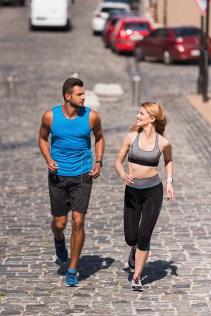 sportswoman and sportsman jogging in city