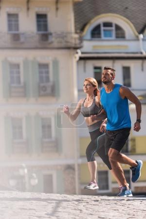 Photo for Athletic sportswoman and sportsman jogging in city at daytime - Royalty Free Image