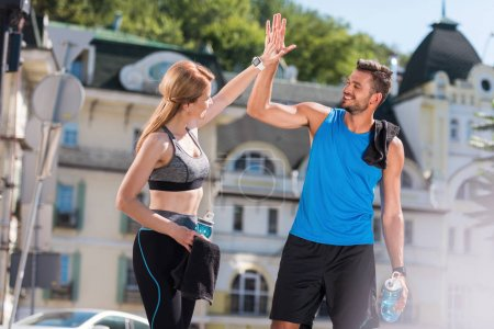 sportswoman and sportsman giving highfive