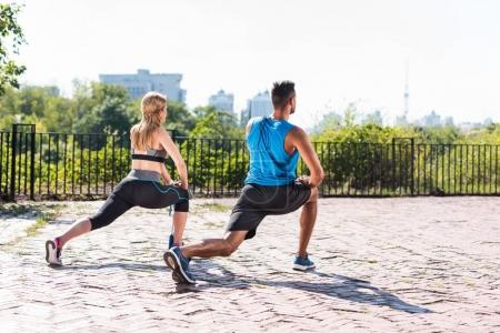 sports couple doing lunge stretch