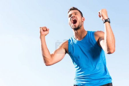 Photo for Excited sportsman celebrating triumph and yelling, with blue sky on foreground - Royalty Free Image