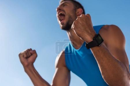 Photo for Excited sportsman with smart watch celebrating triumph and yelling, with blue sky on foreground - Royalty Free Image