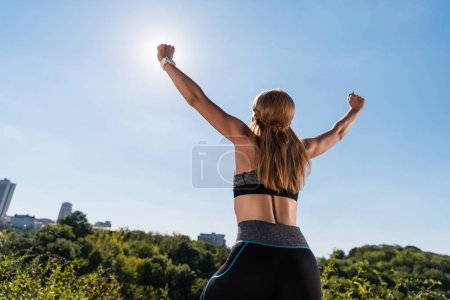 Photo for Back view of sportswoman celebrating triumph, with blue sky on foreground - Royalty Free Image