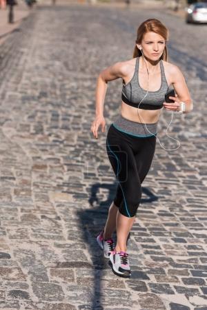 sportswoman running in city