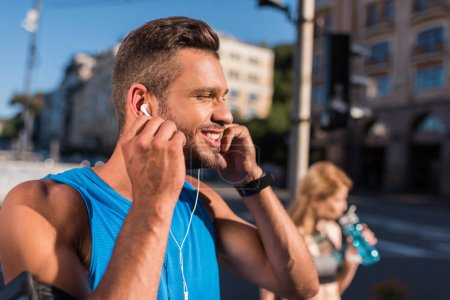 Photo for Smiling sportsman listening music with earphones in city - Royalty Free Image
