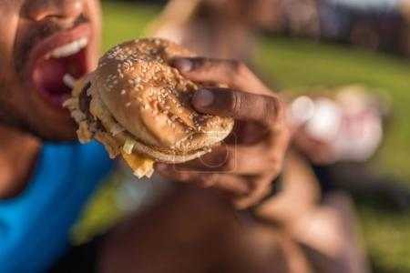 man biting hamburger