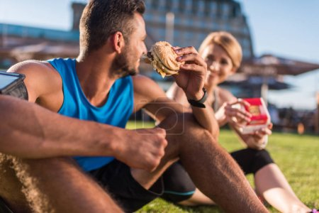 sports couple eating junk food