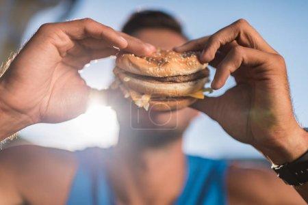 Photo for Close up view of man eating unhealthy hamburger - Royalty Free Image