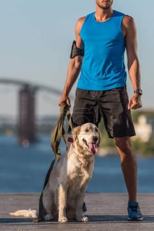 sportsman with dog on quay