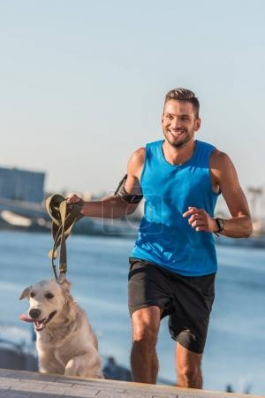 Photo for Happy sportsman jogging with dog in city at daytime - Royalty Free Image