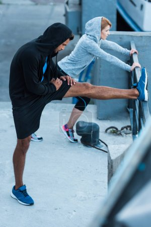 Sportswoman and sportsman stretching in city