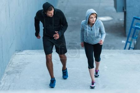 Photo for Athletic sportswoman and sportsman jogging on stairs in city - Royalty Free Image