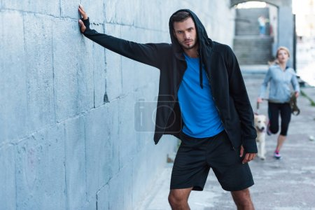 Photo for Sportsman in sportswear posing at wall in city - Royalty Free Image