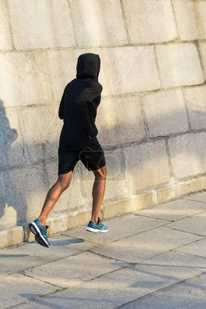 sportsman running at wall
