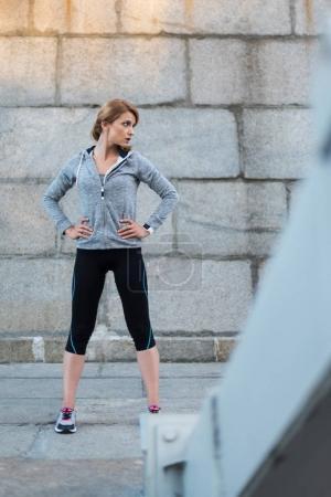 Photo pour Attrayant sportif avec montre intelligente debout au mur - image libre de droit