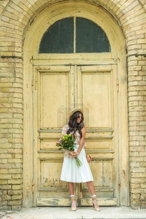 Photo pour Belle jeune femme en chapeau et robe vintage tenant le bouquet de fleurs - image libre de droit