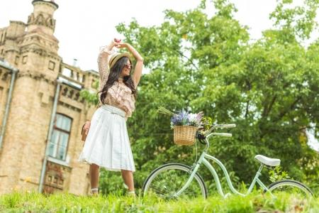 Photo for Low angle view of cheerful pretty girl posing with bicycle in park - Royalty Free Image
