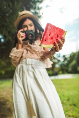 girl photographing watermelon