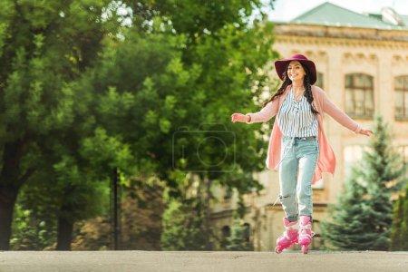 Photo pour Belle jeune femme heureuse CIRC. patins à roulettes dans le parc - image libre de droit
