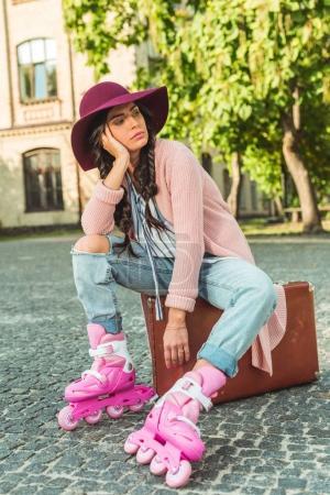 Photo pour Songeuse jeune femme en chapeau et patins assis sur la valise et la recherche. - image libre de droit
