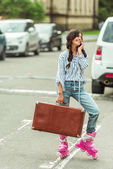 girl in roller skates with smartphone and suitcase