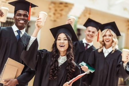 Photo pour Groupe d'étudiants diplômés multiethniques avec des tasses en papier de café - image libre de droit