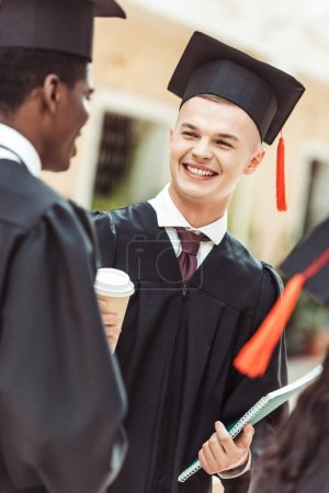 Photo for Multiethnic students in graduation costumes drinking coffee and talking - Royalty Free Image