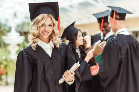 Photo for Beautiful young student girl in graduation costume with multiethnic group of students on background - Royalty Free Image