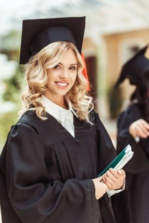 Photo for Beautiful young graduated student girl with notebook - Royalty Free Image