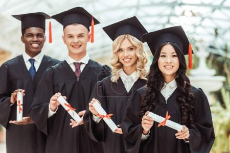 Group of multiethnic students with diplomas