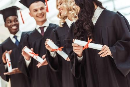 Photo for Happy multiethnic students with diplomas in graduation hats and capes - Royalty Free Image