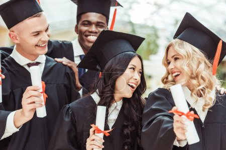 Photo for Group of multiethnic students in graduation costumes with diplomas - Royalty Free Image