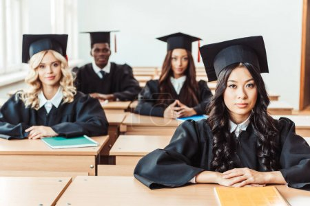 Photo for Graduated multiethnic students sitting at classroom and looking at camera - Royalty Free Image