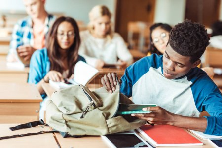 Photo pour Groupe de jeunes étudiants multiéthiques assis en classe - image libre de droit