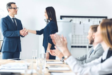boss shaking hand of manageress