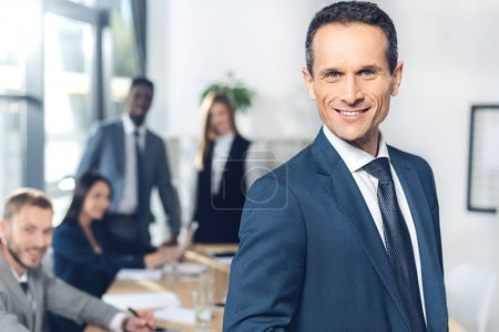 Photo for Handsome businessman looking at camera in conference hall with partners blurred on background - Royalty Free Image