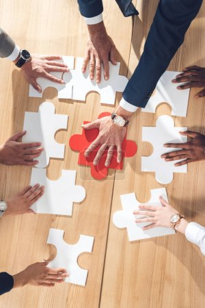 Photo for Top view of businesspeople assembling puzzle on table - Royalty Free Image