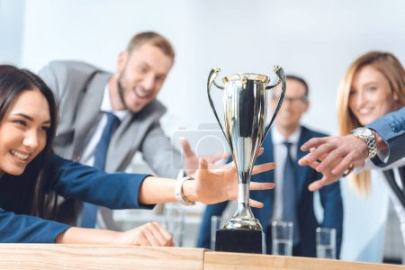 businesspeople trying to catch champion cup