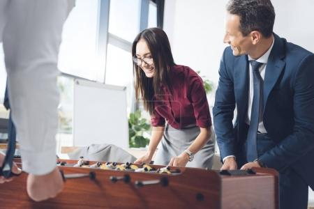 Photo for Happy successful businesspeople playing table football in modern office - Royalty Free Image