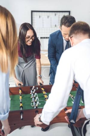 businesspeople playing table football