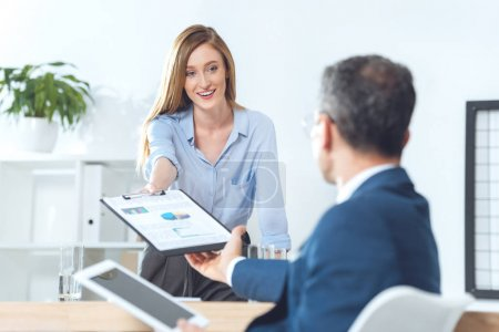Photo for Young attractive businesswoman passing clipboard with documents to partner - Royalty Free Image