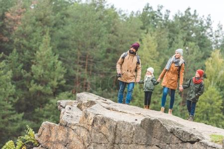 Photo for Family holding hands standing on rock together in autumn forest - Royalty Free Image