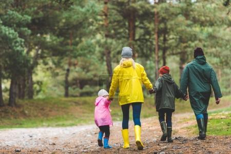Photo pour Vue arrière du parents et enfants, main dans la main ensemble tout en marchant dans la forêt d'automne - image libre de droit