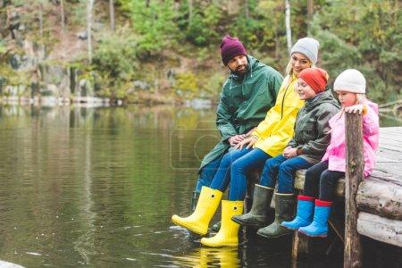 Photo pour Famille heureuse assis ensemble sur un pont en bois à la rivière dans la forêt - image libre de droit