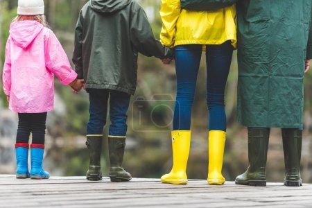 Family standing on wooden bridge