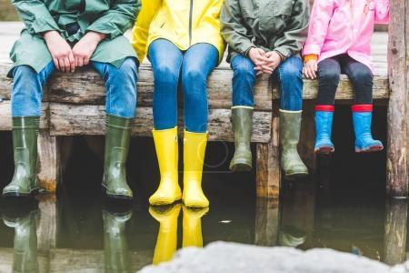 Photo pour Vue partielle de la famille en caoutchouc, bottes assis sur un pont en bois près du lac - image libre de droit