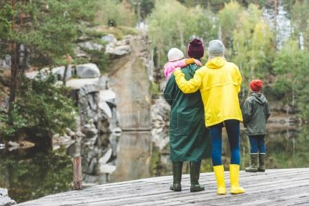 Family standing on bridge in autumn forest