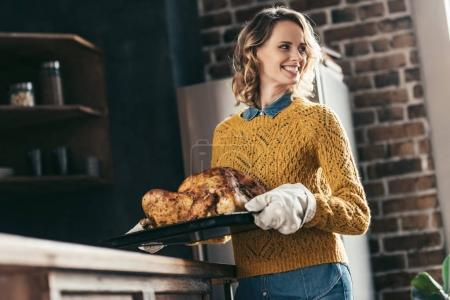 woman carrying tray with turkey